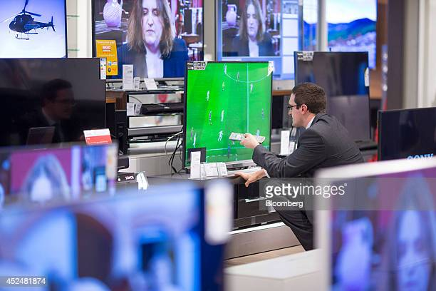 An employee uses a remote control to adjust a flat screen television in the home entertainment section of a John Lewis Plc department store in Milton...