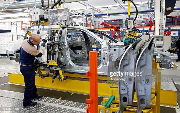 An employee uses a robot as he mounts a rear passenger door onto the bodyshell of a Maserati Quattroporte luxury automobile as it travels along the...