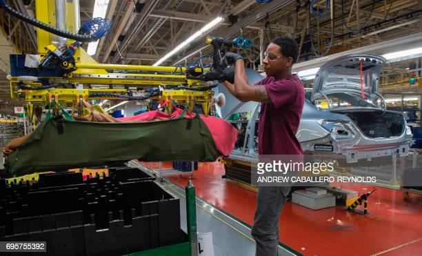 An employee uses a robotic arm to help lift intaernal parts for a MercedesBenz CClass at the MercedesBenz US International factory in Vance Alabama...