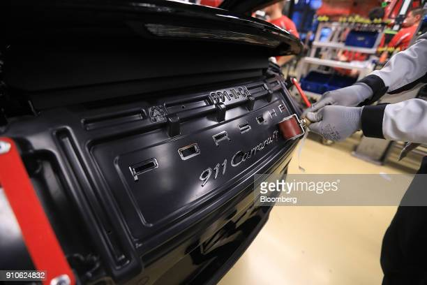 An employee uses a roller to glue a badge on a Porsche 911 Carrera 4S luxury automobile on the production line inside the Porsche AG factory in...