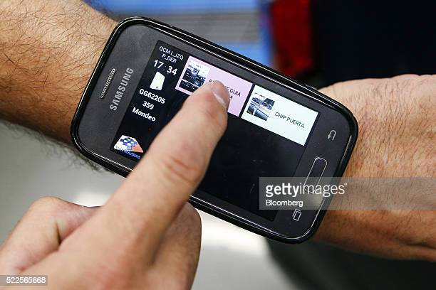 An employee uses a Samsung Electronics Co smartphone on his arm to assist with final quality control checks on completed automobiles at the end of...