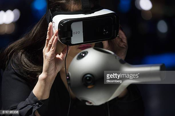An employee uses a Samsung Gear VR virtual reality headset to demonstrate the Ozo a virtual reality camera manufactured by Nokia Oyj at the European...