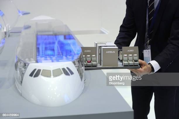 An employee uses a scale model to demonstrate the variations in passenger seating arrangements possible on an Airbus Group A380 multi-deck aircraft...