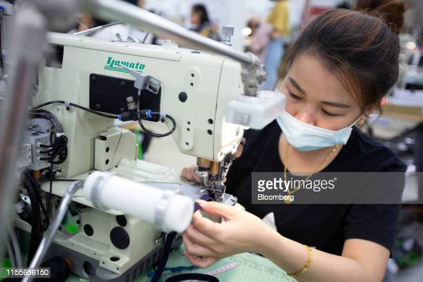 An employee uses a sewing machine inside the sample production room at the EclatTextile Co. Headquarters in Taipei, Taiwan, on Monday, July 8, 2019....