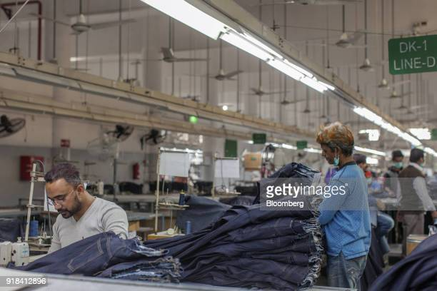 An employee uses a sewing machine to make a pair of jeans in the stitching unit at the Artistic Denim Mills Ltd factory in Karachi Pakistan on...