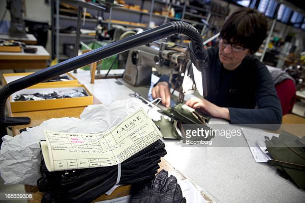 An employee uses a sewing machine to stitch a pair of luxury handmade leather gloves during the manufacturing process at the Causse Gantier factory...