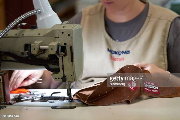 56665d4234f An employee uses a sewing machine while assembling a ball glove at the  Nokona manufacturing facility