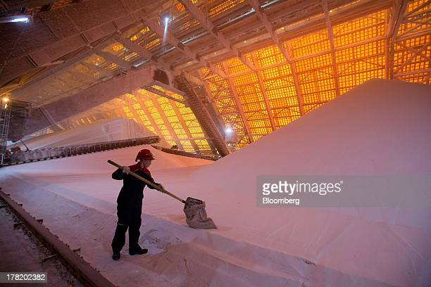 An employee uses a shovel to fill a sack with potassium chloride also known as potash from a processing plant at the OAO Uralkali mine in Berezniki...