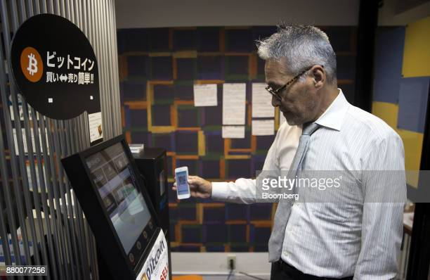 An employee uses a smartphone as he demonstrates how to purchase bitcoins from a bitcoin automated teller machine at the Coin Trader bitcoin retail...