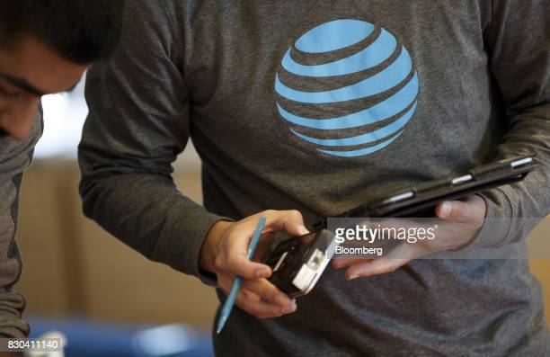 An employee uses a tablet computer at an ATT Inc store in Newport Beach California US on Thursday Aug 10 2017 ATT Inc shares surged the most in more...