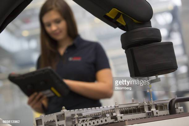 An employee uses a tablet device to control a robotic arm on the automated production line at the Robert Bosch GmbH digital factory in Stuttgart...