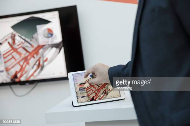 An employee uses a tablet device while demonstrating the Sin Motion lightweight automobile steel design software at the ArcelorMittal research and...