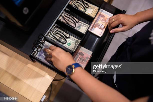 An employee uses a till in the Kinokuniya Co book store at the Aeon Mall in Phnom Penh Cambodia Sunday May 26 2019 Kinokuniya Japan's largest...