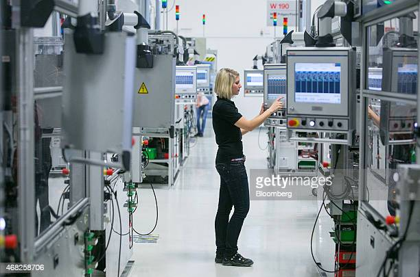An employee uses a touchscreen panel on the automobile gasoline direct injector valve assembly line at the Robert Bosch GmbH plant in Blaichach...