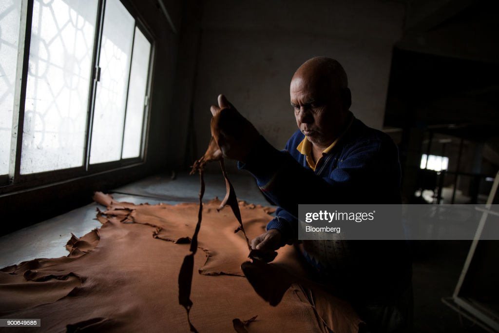 An employee uses a trimming knife to cut a piece of leather at the Sheong Shi Tannery in Kolkata, West Bengal, India on Tuesday, Dec. 26, 2017. India's manufacturing sector grew in December as the Nikkei India Manufacturing Purchasing Managers' Index (PMI) rose to 54.7 from 52.6 in November, with a number above 50 indicating expansion. Photographer: Taylor Weidman/Bloomberg via Getty Images