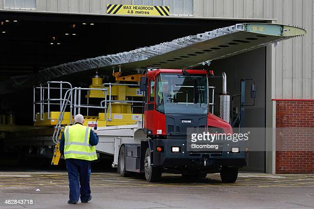 An employee uses a truck to transport an Airbus A330 wing from the Airbus A320/A330 wing assembly building at the Airbus Group NV assembly plant in...