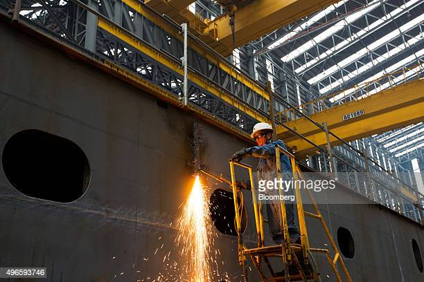 An employee uses a welding torch while working on a ship under construction at the Hyundai Heavy Industries Co shipyard in Ulsan South Korea on...