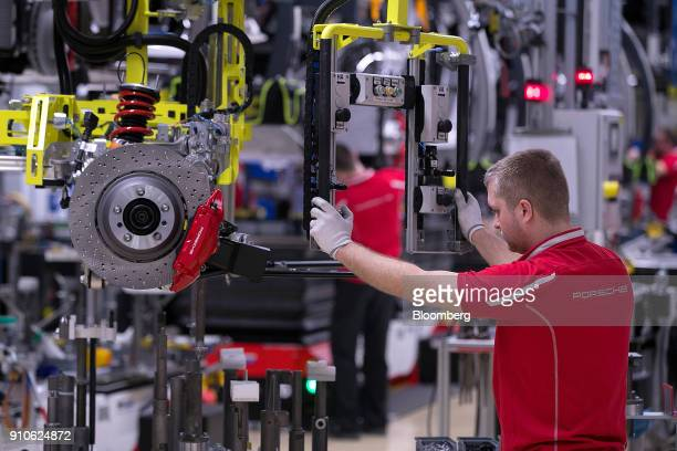 An employee uses a winch control to lift an axle on the production line inside the Porsche AG luxury automobile factory in Stuttgart Germany on...