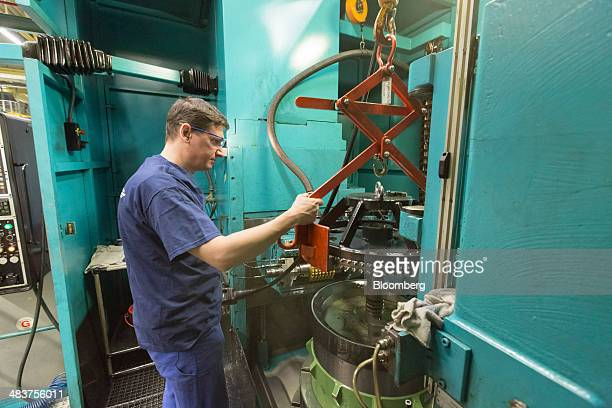 An employee uses a winch to position a cog in a Heidelberg industrial printing press inside the manufacturing hall of Heidelberger Druckmaschinen AG...