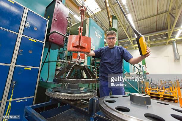 An employee uses a winch to position a cog in the industrial printing press manufacturing hall of Heidelberger Druckmaschinen AG in Wiesloch Germany...