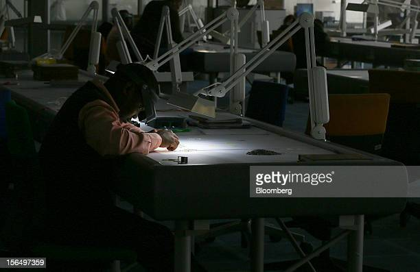 An employee uses an angled light and a magnifier to illuminate uncut diamonds at a sorting table in DTC Botswana a unit of De Beers in Gaborone...