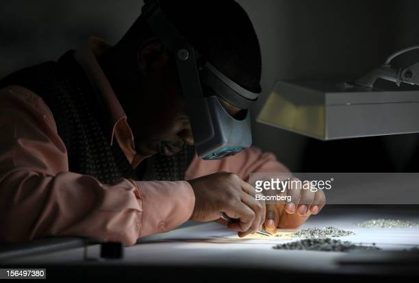 An employee uses an angled light and a magnifier to sort uncut diamonds at a sorting table in DTC Botswana a unit of De Beers in Gaborone Botswana on...