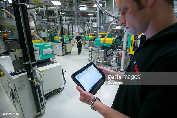 An employee uses an app on a tablet device to control production on the automobile gasoline direct injector valve assembly line at the Robert Bosch...