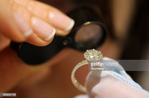 An employee uses an eyeglass to closely examine a cut diamond ring inside a luxury jewelry store operated by Kristall Production Corp in Moscow...