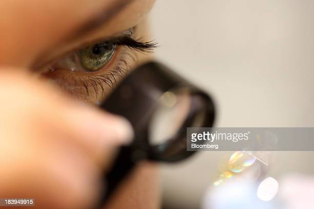 An employee uses an eyeglass to closely examine a diamond ring inside a luxury jewelry store operated by Kristall Production Corp in Moscow Russia on...