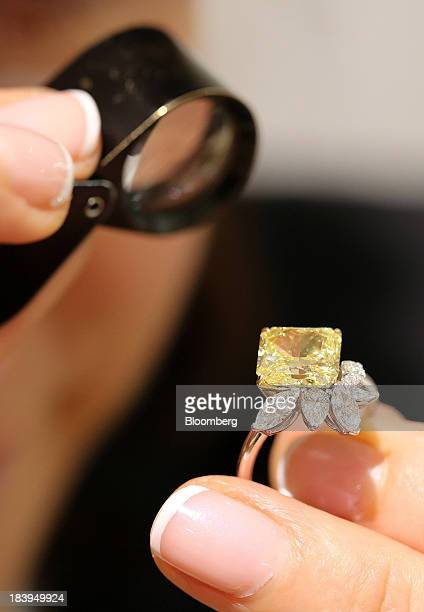 An employee uses an eyeglass to examine a fancy intense yellow radiantcut diamond ring for sale inside a luxury jewelry store operated by Kristall...