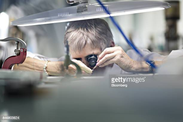 An employee uses an eyepiece to inspect an internal component of a wristwatch at the Zenith a watchmaking unit of LVMH Moet Hennessy Louis Vuitton SA...