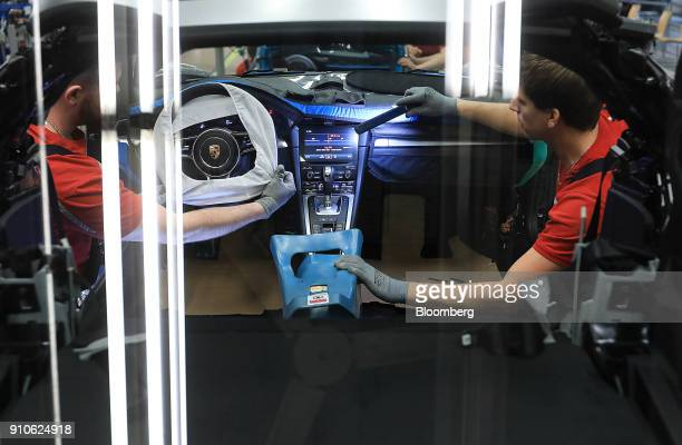 An employee uses an LED light to inspect the dashboard and steering wheel of a Porsche 718 Cayman luxury automobile on the production line inside the...