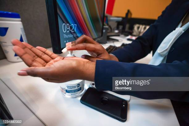 An employee uses hand sanitizer at their desk in the offices of a branch of Metro Bank Plc in London, U.K., on Thursday, Aug. 26, 2021. Some two...