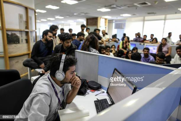 An employee uses headphones while working at a computer as his colleagues gather for a storyboard meeting at the Think and Learn Pvt office in...