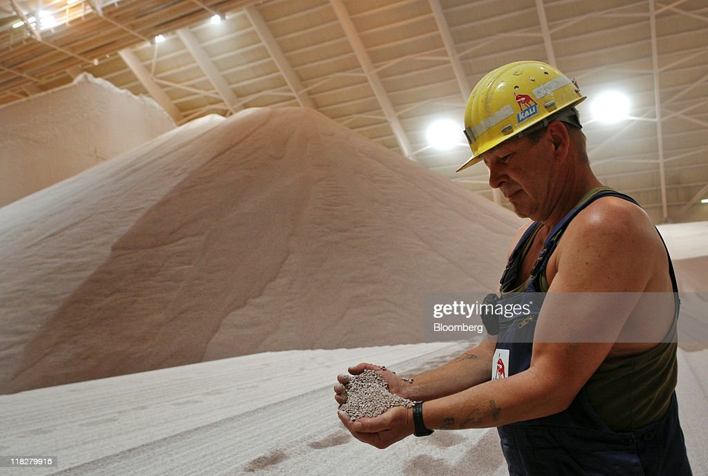 An employee uses his hands to display potash stored in the warehouse in this arranged photograph at the K+S AG potash mine in Unterbreizbach, Germany, on Tuesday, July 5, 2011. K+S AG, Europe's biggest potash producer, dropped 1.3 percent to 53 euros and Yara International ASA, the largest maker of nitrogen fertilizers, slid 4.2 percent to 303.70 kroner as a U.S. Department of Agriculture report showed that U.S. grain acreage and inventories topped analysts' estimates. Photographer: Hannelore Foerster/Bloomberg via Getty Images