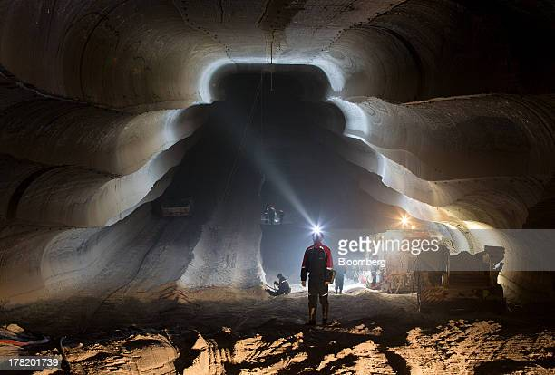 An employee uses the light from a head torch to illuminate the machine cut walls of a potash mine operated by OAO Uralkali in Berezniki Russia on...