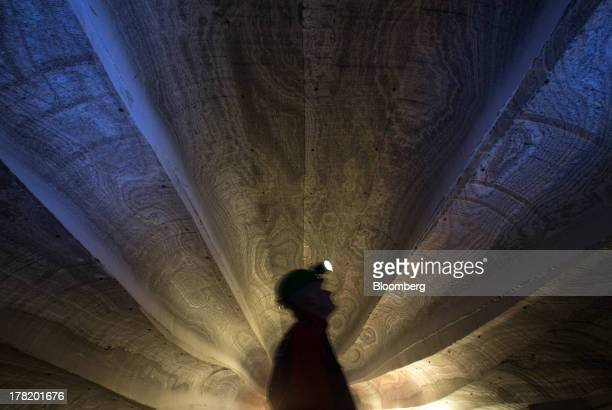 An employee uses the light from a head torch to inspect the machine cut walls of a potash mine operated by OAO Uralkali in Berezniki Russia on Friday...
