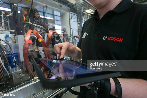 An employee uses the touchscreen of a tablet device to control production on the automobile gasoline direct injector valve assembly line at the...