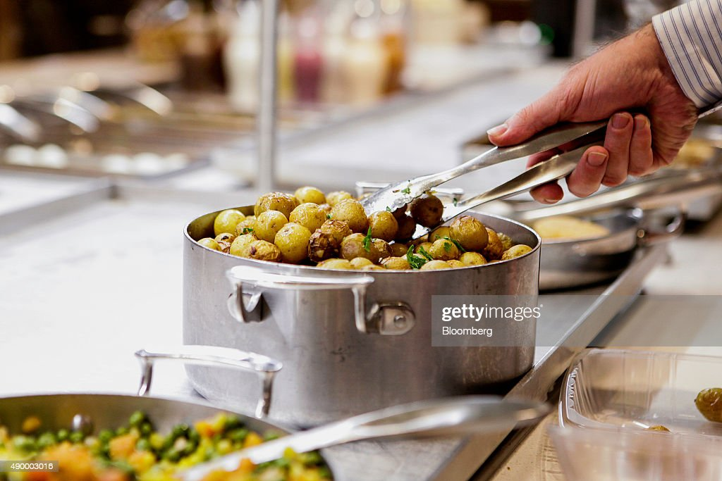 An employee uses tongs to pick up roasted potatoes during lunch in the cafeteria of the Societe Generale SA office in New York, U.S., on Monday, Sept. 14, 2015. Many of Wall Street's biggest banks have revamped their dining facilities in recent years, adding copious amounts of salad and partnering with local businesses to provide a smorgasbord of organic offerings. Photographer: Chris Goodney/Bloomberg via Getty Images
