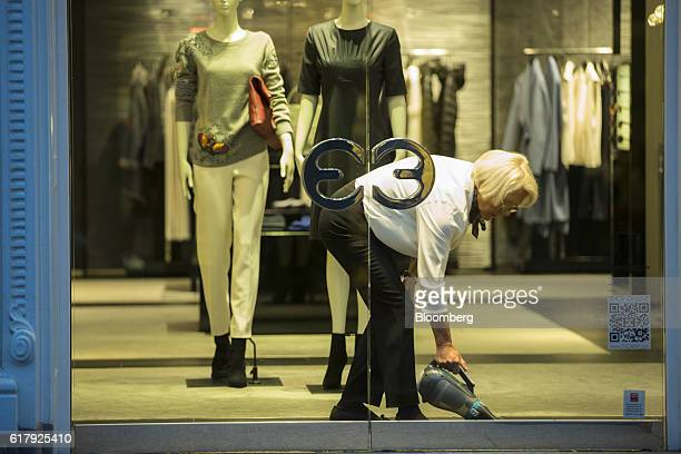 An employee vacuums inside an Escada luxury clothing store in BadenBaden Germany on Monday Oct 24 2016 The world's luxurygoods market stopped growing...
