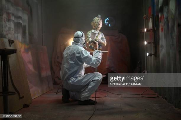 """An employee varnishes an artwork representing the character of 'Tintin' from the plastic artist Christophe Tixier, alias """"Peppone"""", at his workshop..."""