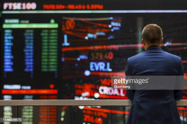 An employee views a FTSE share index board in the atrium of the London Stock Exchange Group Plc's offices in London, U.K., on Wednesday, May 29,...