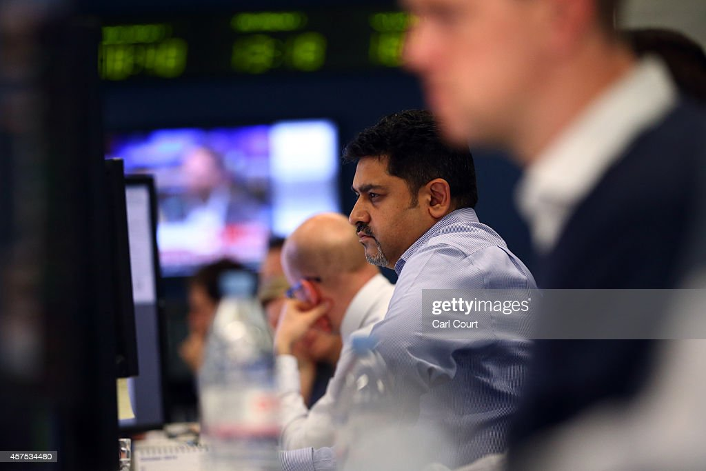 An employee views trading screens at the offices of Panmure Gordon and Co on October 20, 2014 in London, England. Markets stabilised over the weekend following global turbulence amid fears over the Ebola virus and global economic concerns.