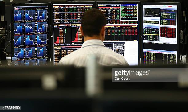 An employee views trading screens at the offices of Panmure Gordon and Co on October 20, 2014 in London, England. Markets stabilised over the weekend...