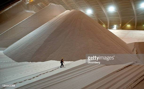 An employee walks across a large mound of potash stored in the warehouse at the KS AG potash mine in Unterbreizbach Germany on Tuesday July 5 2011 KS...