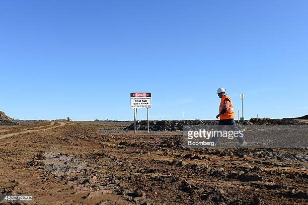 An employee walks across the runofmine pad at Evolution Mining Ltd's gold operations in Mungari Australia on Wednesday Aug 5 2015 A declining gold...