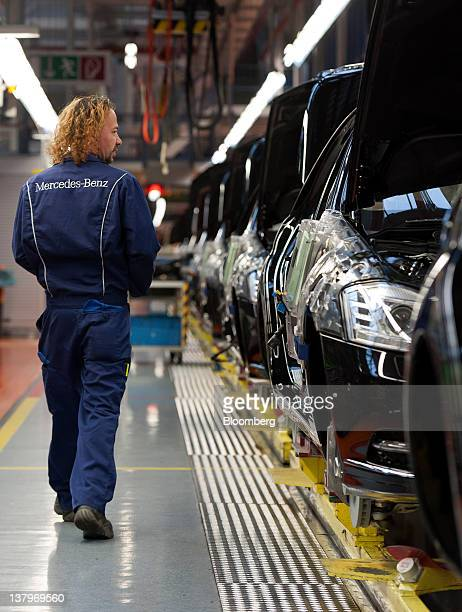An employee walks alongside Daimler AG MercedesBenz Sclass automobiles as they travel along the production line inside the company's factory in...