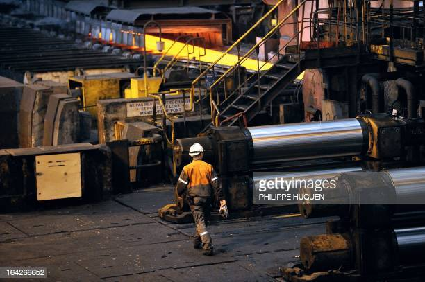 An employee walks at the Arcelor Mittal steel plant in GrandeSynthe northern France on March 21 2013 AFP PHOTO PHILIPPE HUGUEN