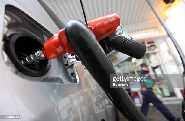 An employee walks behind a car being filled with gasoline at a gas station in Tokyo Japan on Thursday Feb 24 2011 Oil advanced for a sixth day in New...