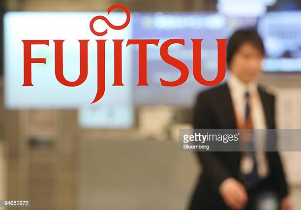 An employee walks behind the logo for Fujitsu Ltd at the company's offices in Tokyo Japan on Tuesday Dec 4 2007 Fujitsu Ltd Japan's biggest...